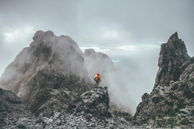 male mountaineer standing on top of a mountain in a rugged lands