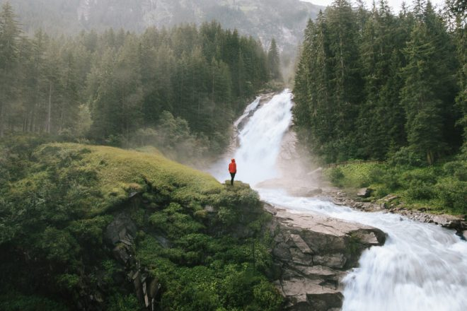 young man standing in front of a beautiful waterfall