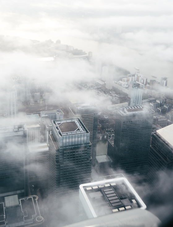 View over the skyscrapers of central London. Soft focus due to fog on aeroplane glass.